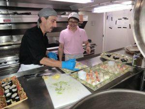 船で寿司を盛り付ける研究者とシェフ